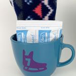gift mug filled with scarf and hot chocolate packet