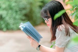 girl with glasses reading book outside